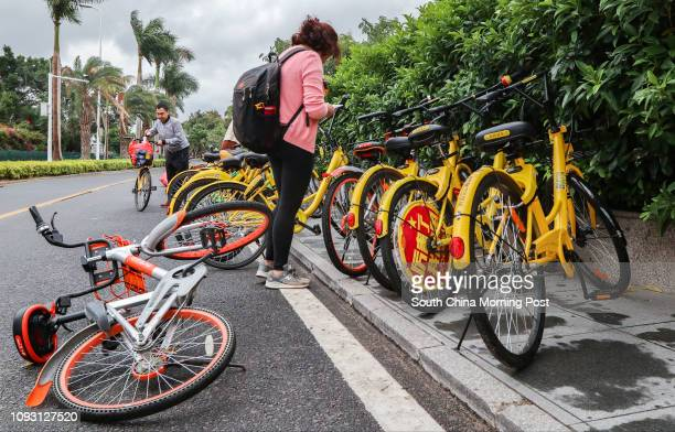 A woman prepares to ride OFO a bikesharing bicycle while Mobike another bikesharing company lays on the floor in Xiamen Fujian Province in...
