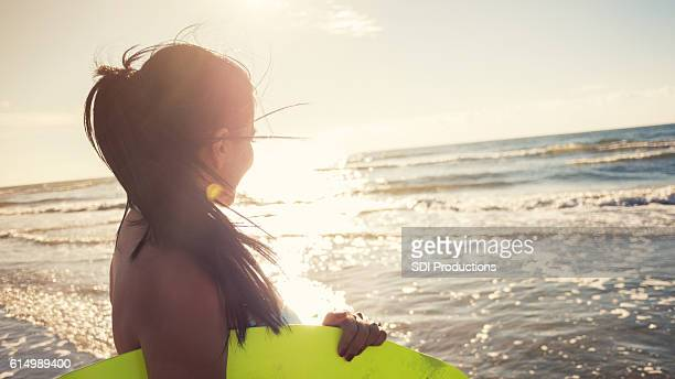 woman prepares to surf at sunset - galveston stock pictures, royalty-free photos & images
