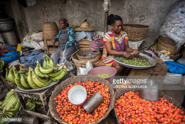 A woman prepares turkey berries to sell at her shop in Makola market Accra June 28 2018