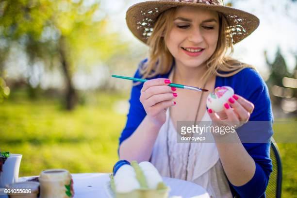 Vrouw voorbereiden en paaseieren schilderen voor vakantie in tuin