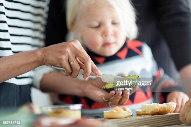 Woman preparing avocado for boy