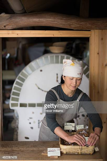 A woman preparing baked goods in a shop