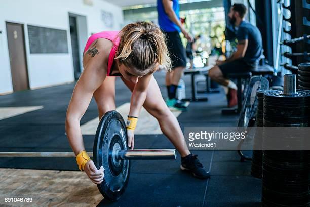 Woman preparing barbell in gym