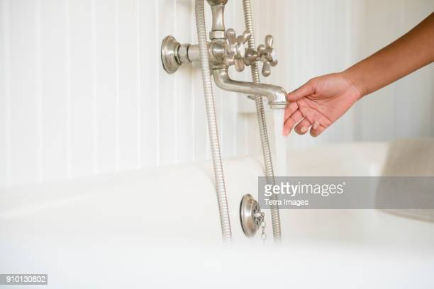 Woman preparing bath, touching water from faucet
