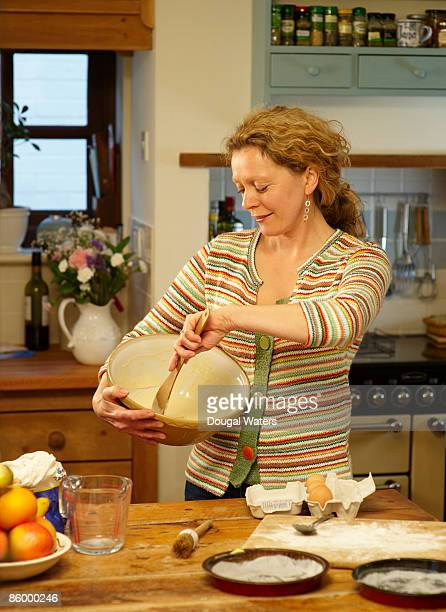 Woman preparing cake mixture in kitchen.