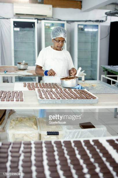 woman preparing chocolate in a chocolate factory - chocolate factory stock pictures, royalty-free photos & images