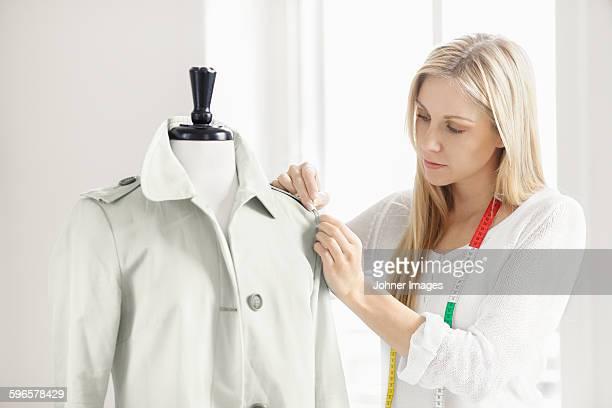 woman preparing coat on mannequin - västra götalands län stockfoto's en -beelden