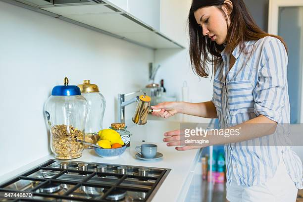 Woman preparing coffee at home in the kitchen
