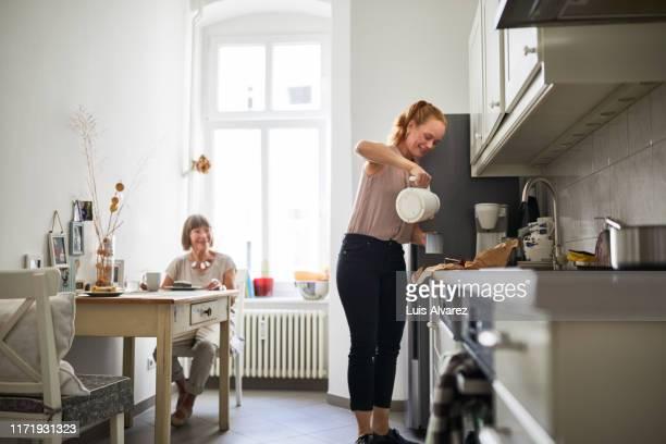 woman preparing coffee for senior woman at dining table - gezondheidszorg beroep stockfoto's en -beelden