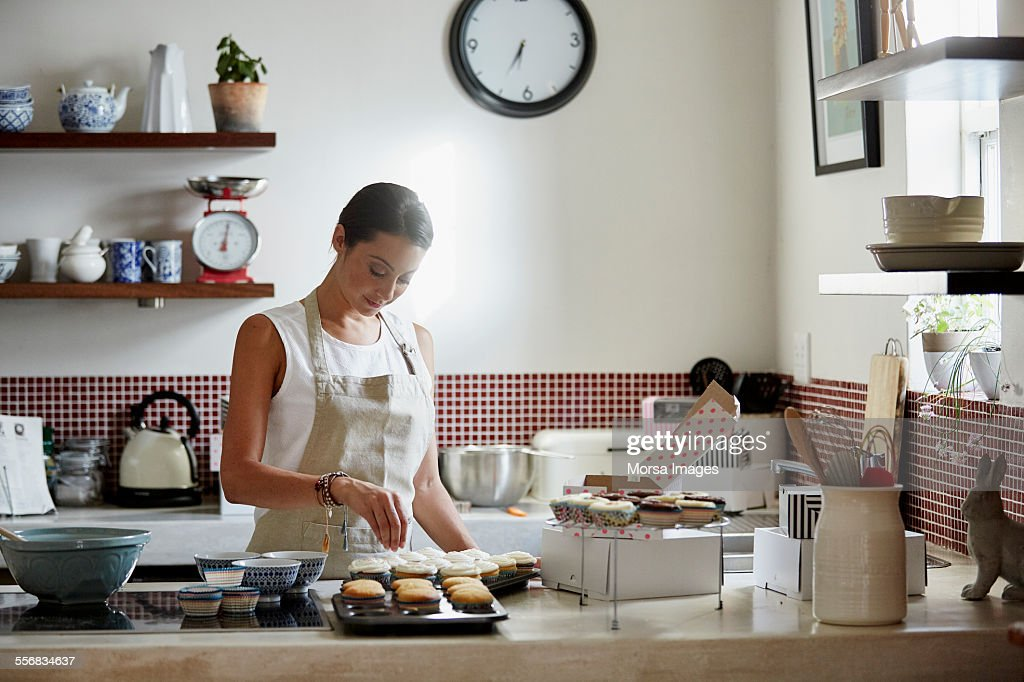 Woman preparing cupcakes in kitchen : Stock Photo