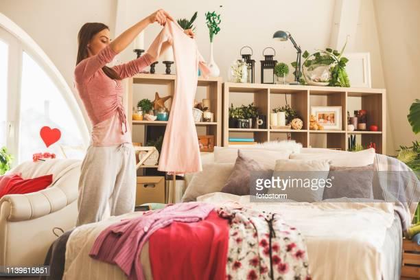 vrouw bereiden dagelijkse outfit in de slaapkamer - kleding stockfoto's en -beelden