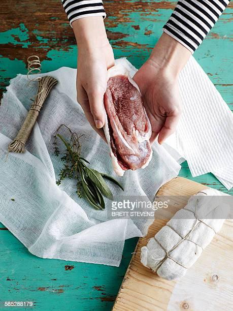 Woman preparing duck prosciutto step 3, salted duck breast in muslin with bouquet garni