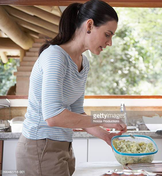 Woman preparing food in kitchen, side view