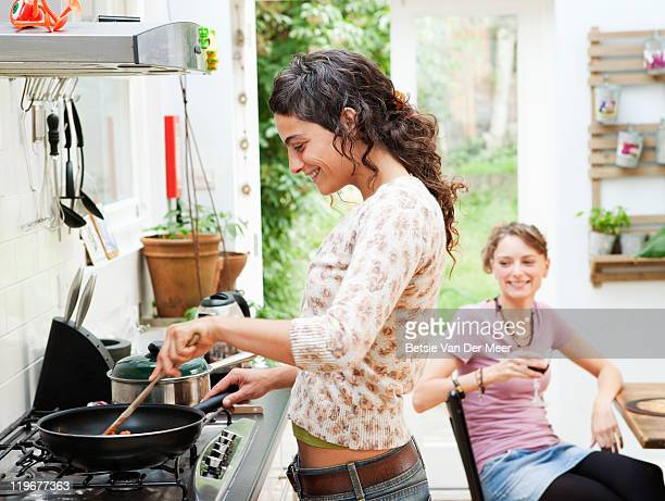 Woman preparing food while talking to friend.