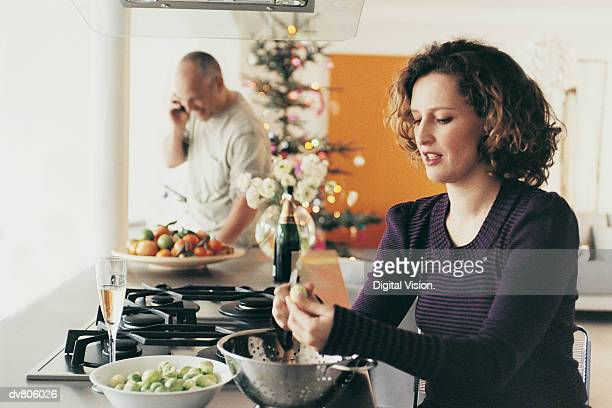 Woman Preparing Food with a Man in the Background on the Phone