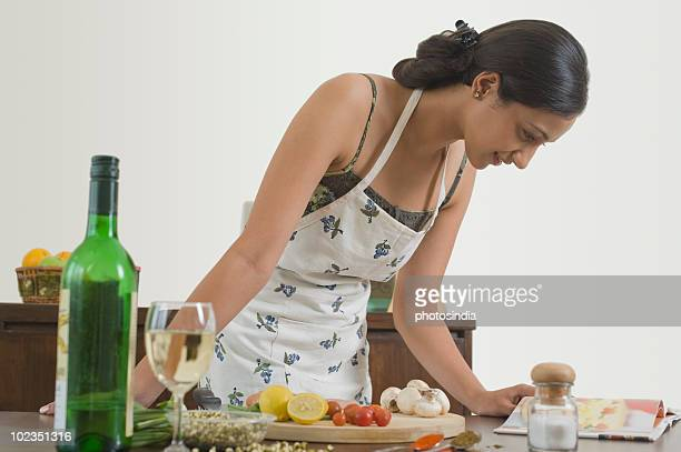Woman preparing food with the help of a cookbook