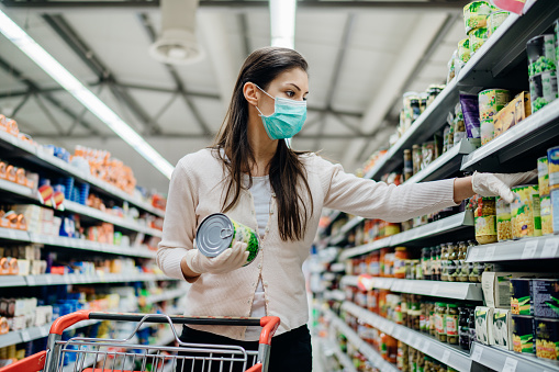 Woman preparing for pathogen virus pandemic spread quarantine.Choosing nonperishable food essentials.Budget buying at a supply store.Pandemic quarantine preparation.Emergency to buy list 1218500852