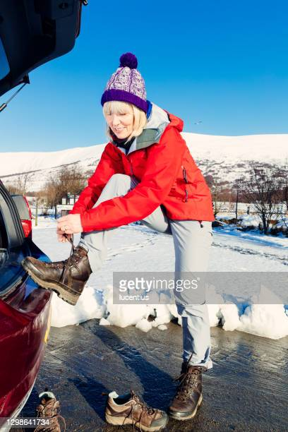 woman preparing for snowy hike in scottish highlands - cold temperature stock pictures, royalty-free photos & images