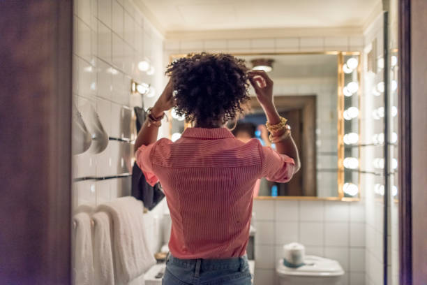 woman preparing hair in bathroom - preparation stock pictures, royalty-free photos & images