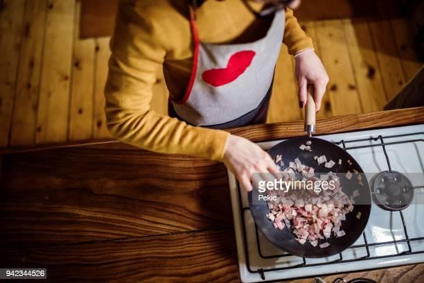 Woman preparing ham in the cooking pan