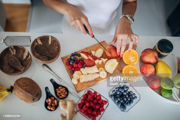 キッチンで健康的な朝食を準備する女性 - 果物の盛り合わせ ストックフォトと画像