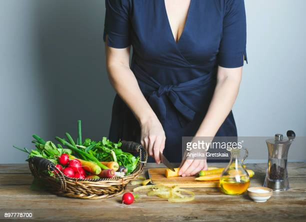 woman preparing healthy food and cutting fresh carrots on wooden board - farm to table stock photos and pictures