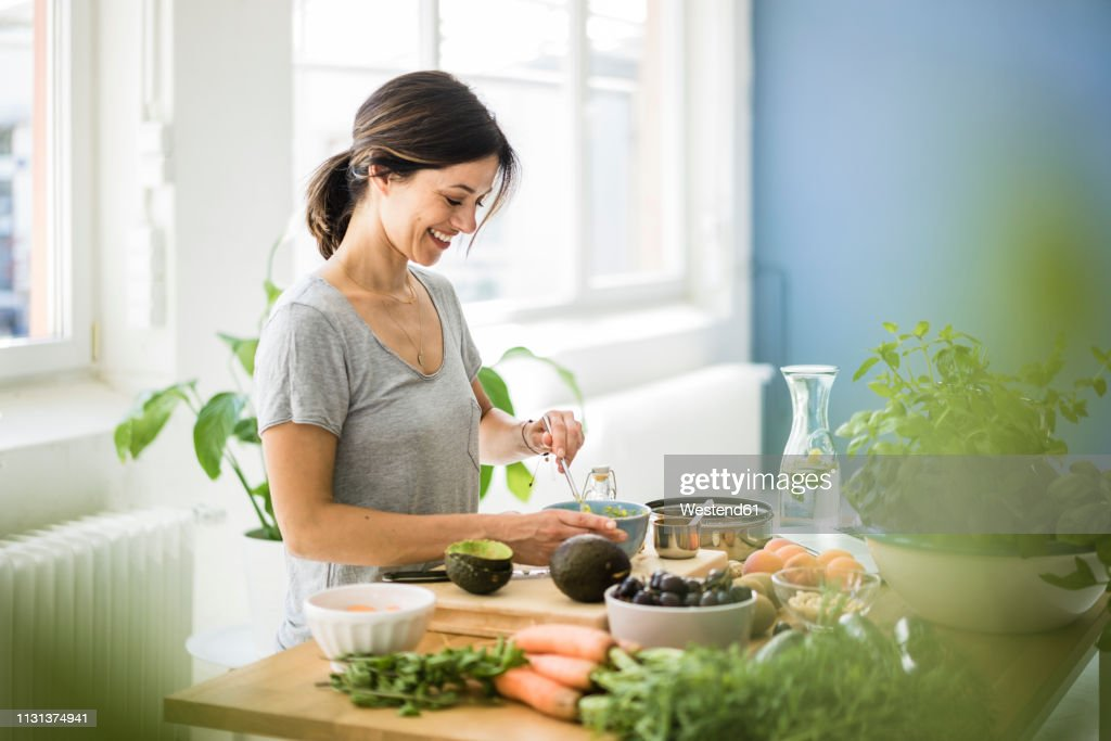 Woman preparing healthy food in her kitchen : Stock Photo