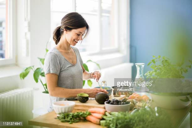 woman preparing healthy food in her kitchen - wohlbefinden stock-fotos und bilder