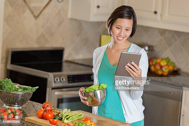 Woman preparing healthy meal while reading recipe on digital tablet