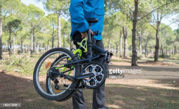 woman preparing her folding bicycle outdoors in forest. - foldable stock pictures, royalty-free photos & images