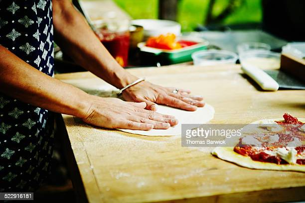 Woman preparing homemade dough for pizza