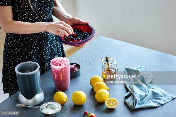 Woman preparing juice with fruits in the kitchen