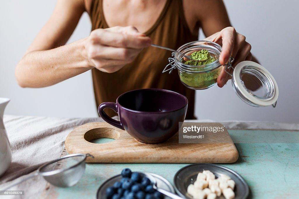 Woman preparing matcha latte at home : Stock Photo