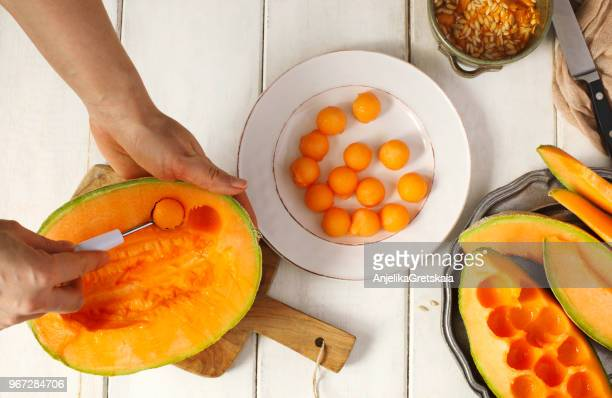 woman preparing melon balls with a cantaloupe melon - muskmelon stock pictures, royalty-free photos & images