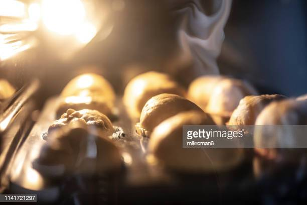 woman preparing muffins and putting it into oven - 焼いた ストックフォトと画像