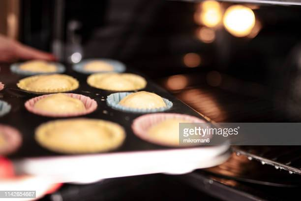 woman preparing muffins and putting it into oven - baking stock pictures, royalty-free photos & images