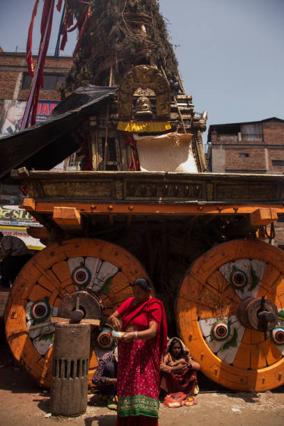 A woman preparing offerings dressed in a traditional sari at the base of an ornate chariot celebrating the Bunga Dyo Jatra Festival in Patan, Kathmandu, Nepal.
