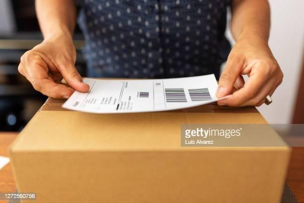 woman preparing package for online delivery - schiffsfracht stock-fotos und bilder