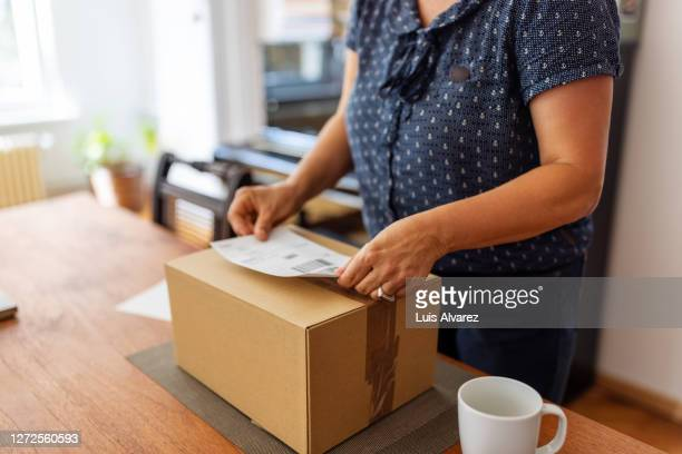 woman preparing package for shipping - independence stock pictures, royalty-free photos & images