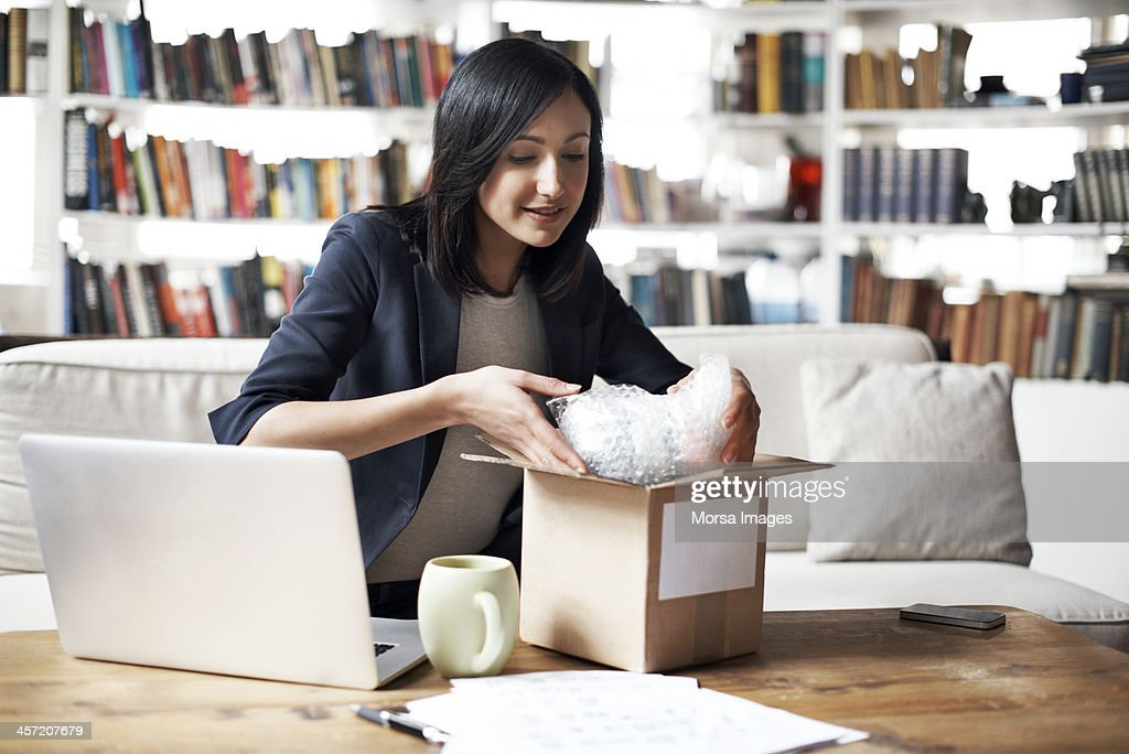 Woman preparing parcel for shipment : Stock Photo