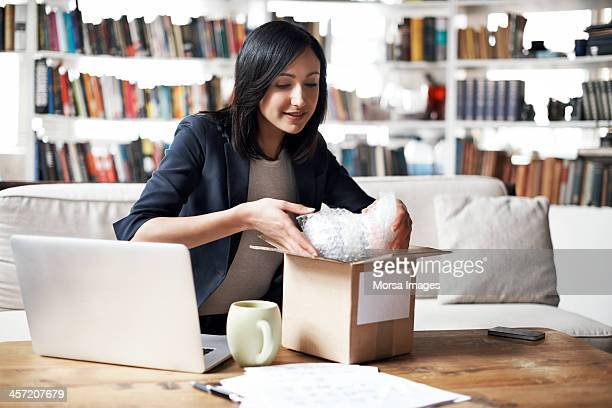 woman preparing parcel for shipment - sending stock pictures, royalty-free photos & images