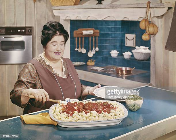 Woman preparing pasta with meatballs in kitchen