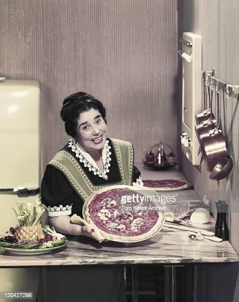 Woman preparing pizza in kitchen