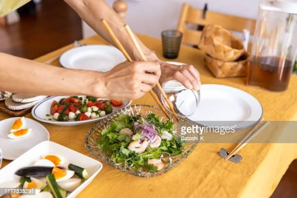 ホームパーティーのためのサラダを準備している女性 - 自家製 ストックフォトと画像