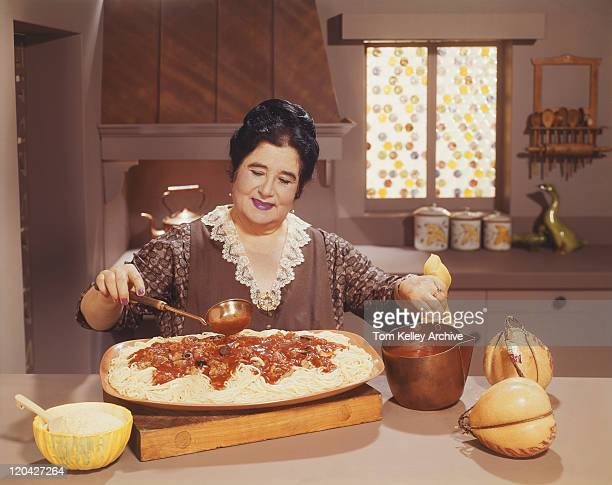 woman preparing spaghetti dish with sauce in kitchen - big tom stock pictures, royalty-free photos & images