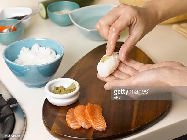Woman preparing sushi at table