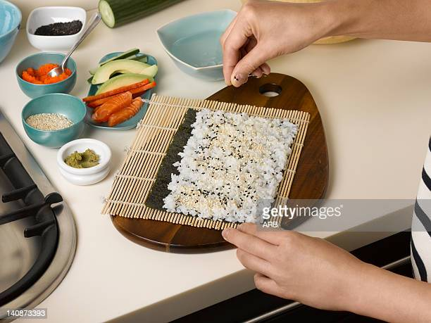 Woman preparing sushi roll at table