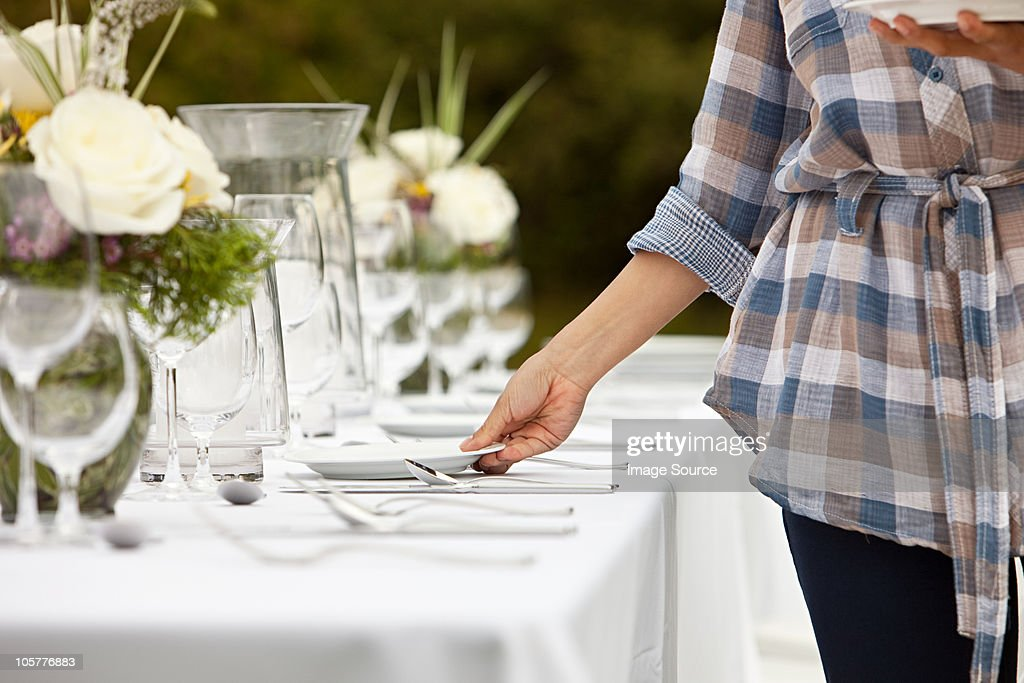Woman preparing table for dinner party in a field : Stock Photo