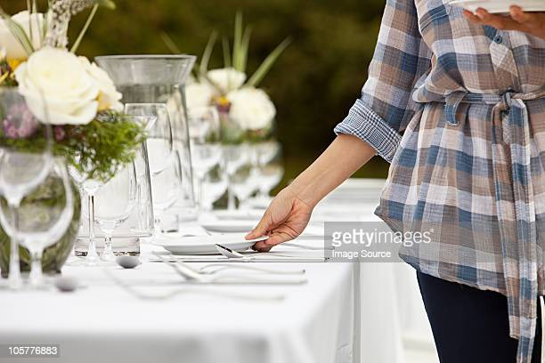 Woman preparing table for dinner party in a field