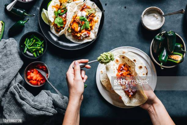 woman preparing tasty vegan tacos - vegetarian food stock pictures, royalty-free photos & images